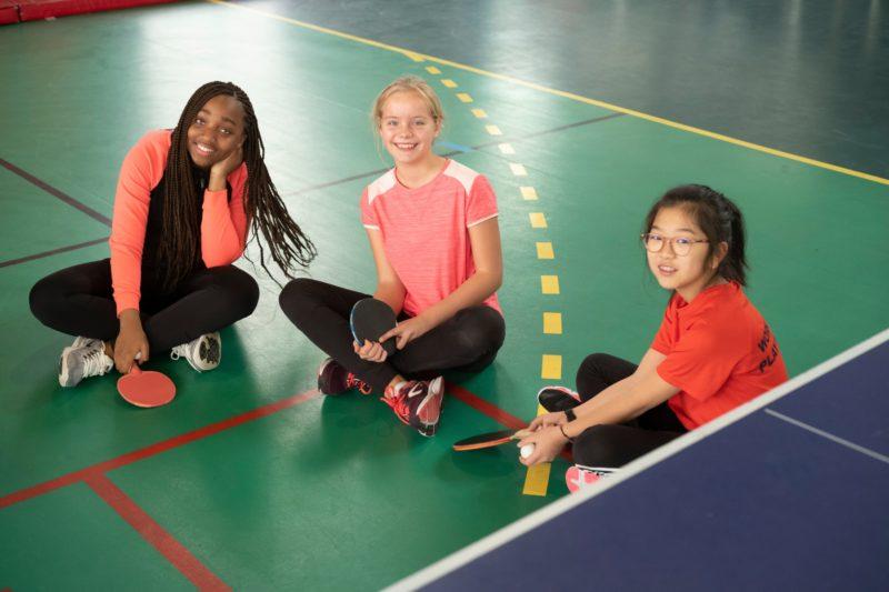 Trois élèves assises par terre dans un gymnase