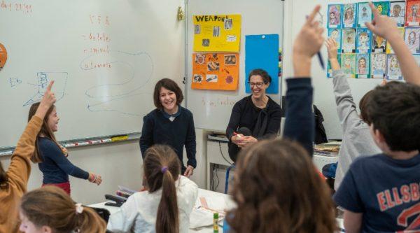 Elèves en cours d'anglais et levant la main