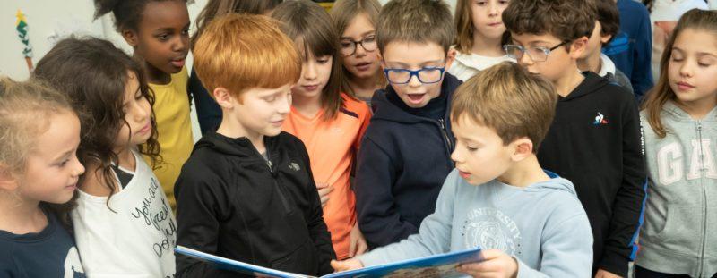 Photo de jeunes élèves lisant ensemble à l'école de Paris