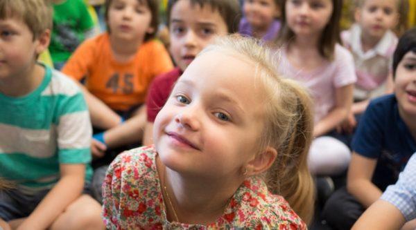 Photo d'une élève souriante et assise par terre en classe