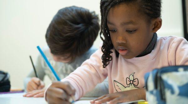 Photo d'une élève écrivant à l'École Jeannine Manuel de Paris
